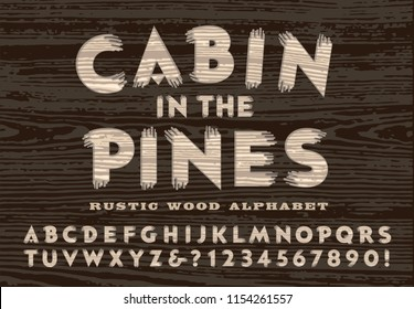 A rustic carved wood alphabet in the style that might be seen on a cabin door or a forest service sign