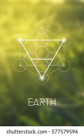 Sacred geometry Earth element symbol inside Metatron Cube and Flower of Life in front of natural blurry background.