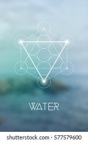 Sacred geometry Water element symbol inside Metatron Cube and Flower of Life in front of natural blurry background.