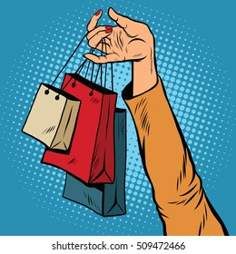 Sale, bags packages in the hands of women, pop art retro vector. Black Friday and holiday sales. A customer in the store