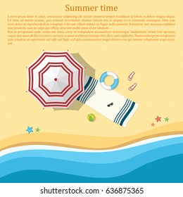 Sandy beach with an umbrella and beach accessories. Top view. Summer background. Place for the test.