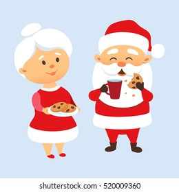 Santa Claus eating a cookies and drinking milk with his wife. Mrs. Santa treat and feed husbant cookies. Xmas tradition. Cute family couple. Mother and Father Christmas