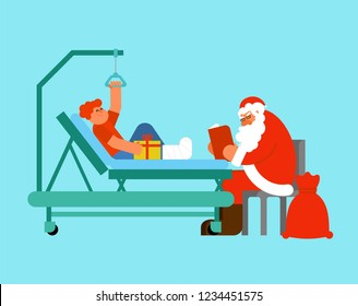 Santa Claus Visits in hospital. Grandfather reads book and gives gift. Boy with broken leg. Child on Hospital bed. Christmas in hospital. Medical care