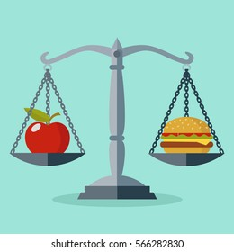 Scales with red apple and hamburger showing balance between healthy and unhealthy food