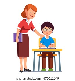 School teacher standing watching, helping, encouraging her student putting hand on his shoulder. Boy kid in glasses sitting at the desk and writing in exercise book. Flat vector illustration isolated.