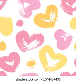 Seamless background with hearts in pink and yellow tones. Expressive dry brushes.
