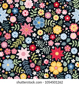 Seamless ditsy floral pattern with bright colorful flowers and leaves on black background in naive folk style. Summer template for fashion prints in vector.