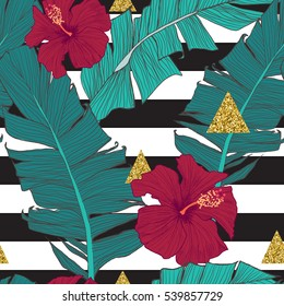 Seamless pattern with banana leaves, tropical flowers and geometrical golden elements