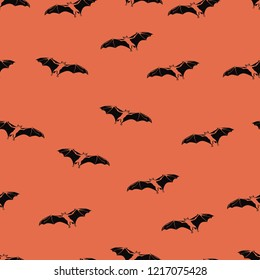 Seamless pattern of black vampire bats on orange background