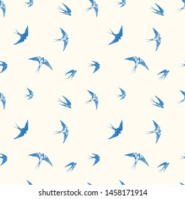 Seamless pattern with blue flying swallow birds on neutral light yellow background