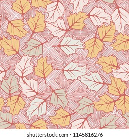 A seamless pattern consisting of chaotically located woody leaves. The leaves are on the background of the formations of parquet-like slabs.