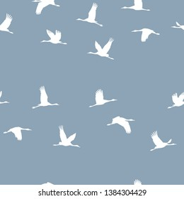 Seamless pattern with a flock of white cranes on a blue background. Vector.