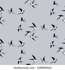 Seamless pattern of four colored swallow silhouettes on a light grey background. Flying birds in different views. Vector Design element.