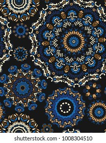 Seamless pattern with a Psychedelic kaleidoscope footage. Mandala ornament. Stylized blue and brown flowers on a black background. Floral motif. Complex flourish weave medallion. Vector illustration.