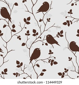 Seamless pattern with silhouette of birds sitting on twigs. Vector background with branches of tree. Decorative vintage wallpaper with birds and leaves