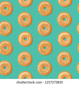 Seamless pattern with top view of fresh bagels, white and brown sesame seeds on top. Delicious breakfast. Vector seamless pattern.