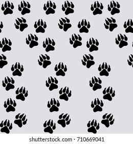 Seamless texture. Black traces of paws on a lilac background