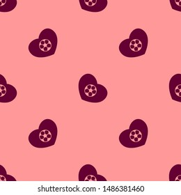 Seamless two color maroon football heart flat pattern on light salmon background.