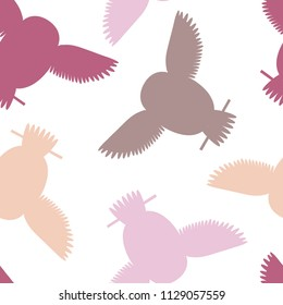 Seamless vector pattern with brown, maroon, pink and orange owls. Repetitive background with vector flat multicolored birds. Owls in the repetitive seamless vector pattern.