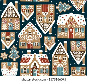 Seamless vector pattern with cute gingerbread houses and cookies on dark blue background. Perfect for textile, wallpaper or print design.