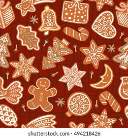 Seamless vector pattern with gingerbread cookies on red background. Christmas ornament