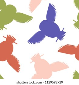 Seamless vector pattern with green, orange, pink and blue owls. Repetitive background with vector flat multicolored birds. Owls in the repetitive seamless vector pattern.