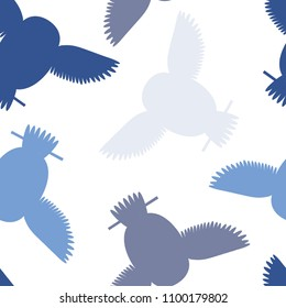 Seamless vector pattern with grey, blue owls. Repetitive background with vector flat multicolored birds. Owls in the repetitive seamless vector pattern.