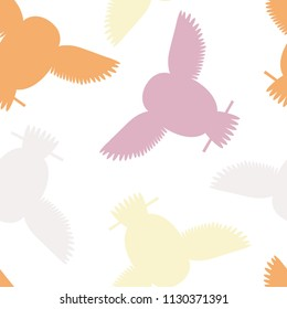 Seamless vector pattern with grey, orange, pink and yellow owls. Repetitive background with vector flat multicolored birds. Owls in the repetitive seamless vector pattern.