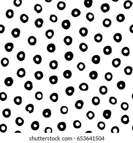 Seamless vector pattern with hand drawn black circles scattered on white background. Modern abstract design for print or textile.