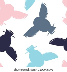 Seamless vector pattern with pink, blue, grey owls. Repetitive background with vector flat multicolored birds. Owls in the repetitive seamless vector pattern.