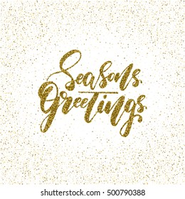 Seasons greetings - ink freehand lettering with golden texture. Modern brush calligraphy, isolated on the golden star shape confetti background.