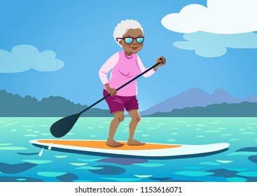 Senior African American woman on a stand up paddle board. Cute grandma wearing rash guard and shorts paddling on calm water, trees and mountains in the background. Healthy active lifestyle for seniors