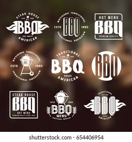 Set of barbecue labels and emblems. White print on blurred background