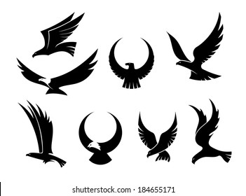 Set of black silhouettes of graceful flying eagles logo with their outspread wings for heraldry and hunting design