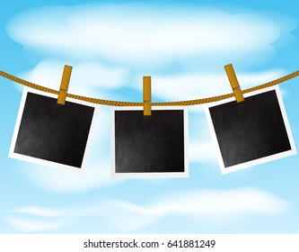 Set of blank photo frames hanging on the rope with wood pins on sky background