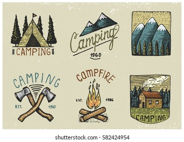 set of engraved vintage, hand drawn, old, labels or badges for camping, hiking, hunting with tent, axe and campfire with mountains.