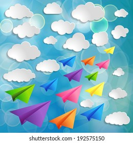 Set of flying colorful paper airplanes with clouds on the blue blurred background