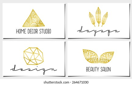 A set of four modern and elegant business card templates in white, gold and black. Hand drawn golden design elements, feathers, leaves, triangle, geometric shapes.