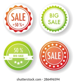 Set of four round sale labels in red and green.