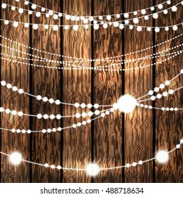 Set of Glowing White String Christmas Lights for Xmas Holiday Greeting Cards Decoration on Wooden Background. Vector