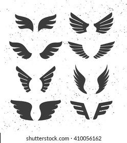 Set of monochrome open wings for badges and signs. Vector symbolic black wings isolated on white. Silhouettes of stylized flapping wings.