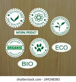 Set of Natural Organic product badges on wood background.