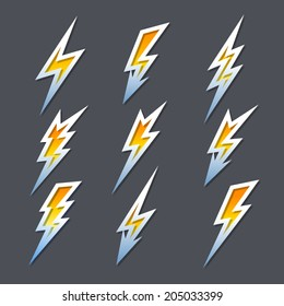 Set of nine different fiery orange cartoon zigzag lightning bolts or electricity icons in different shapes with metallic outlines
