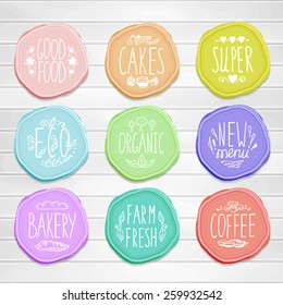 Set of retro badges on a wood background. Hand-drawn lettering and elements. Creative colored handmade food labels with inscriptions in vintage style.