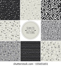 Set of seamless patterns in gray tones with doodled dots, arrows, hearts,stripes,circles,stars, triangles and other geometric symbols, vector repeating texture