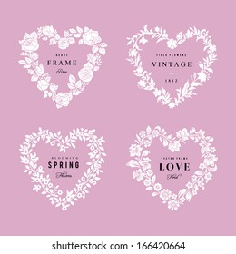 Set of vector floral frames in the shape of heart. Four White silhouettes of flowers on a pink background. Design elements.