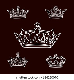 Set white crowns on black background. Vector Icons.