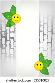 Sheet of paper and green leaves with smiles on brick wall