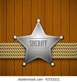 Sheriff's badge on a wooden background.