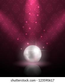Shiny pearl under spotlights on ornate wallpaper background